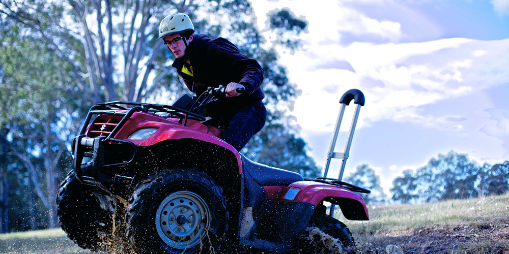 Farmer on a quad bike fitted with a roll bar