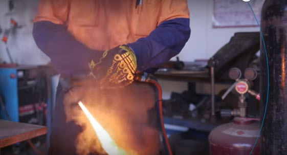 A man with a burning oxy-acetylene torch
