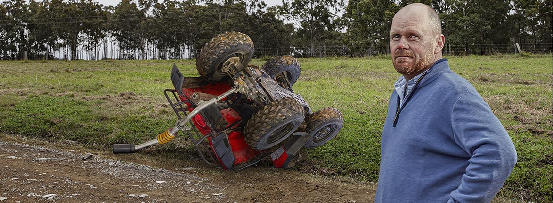 A campaign image for roll bars on quad bikes showing a farmer with an overturned quad bike