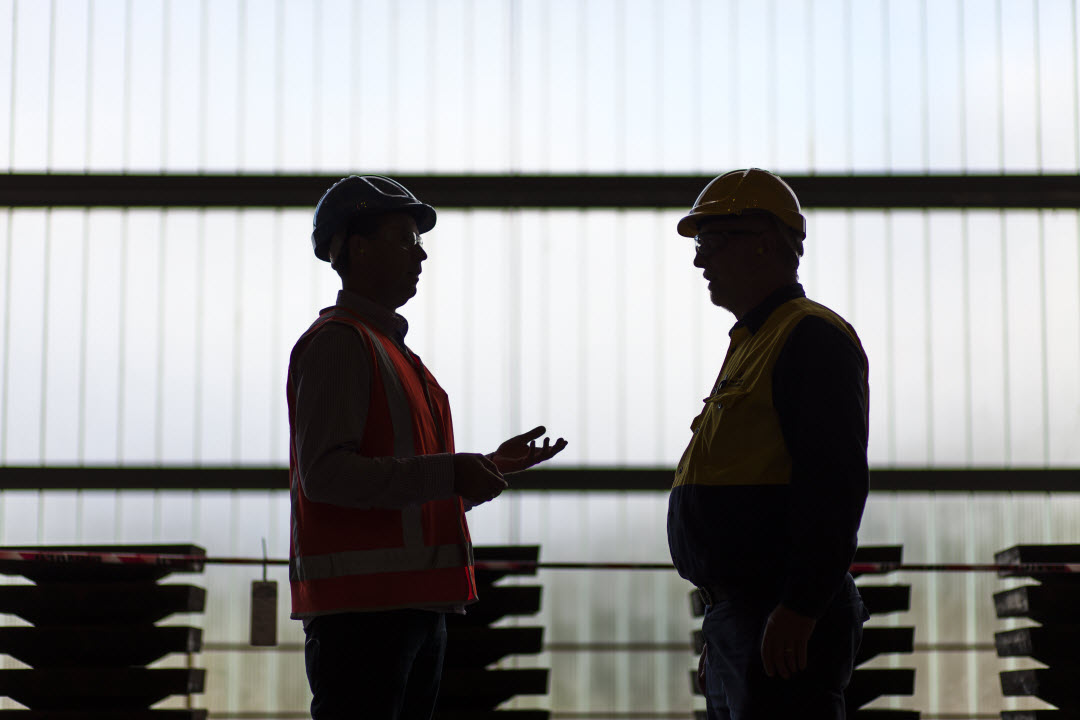 two men talking with hard hats on