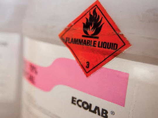 A white drum with a flammable liquid warning sign