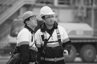 2 men with safety harnesses looking up