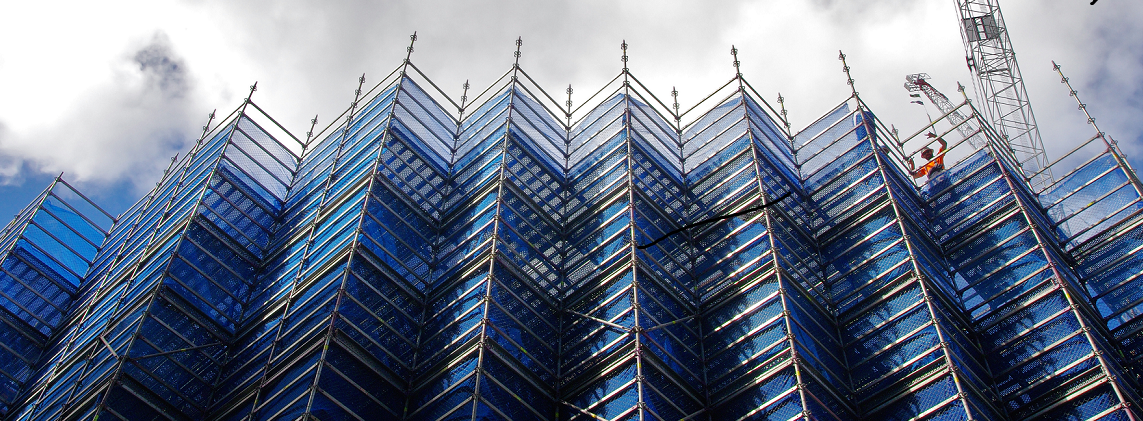 Scaffolding on a large building with a blue sky