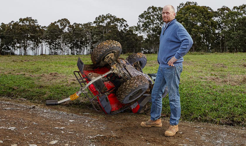 A farmer in the foreground with his overturned quad bike in the background