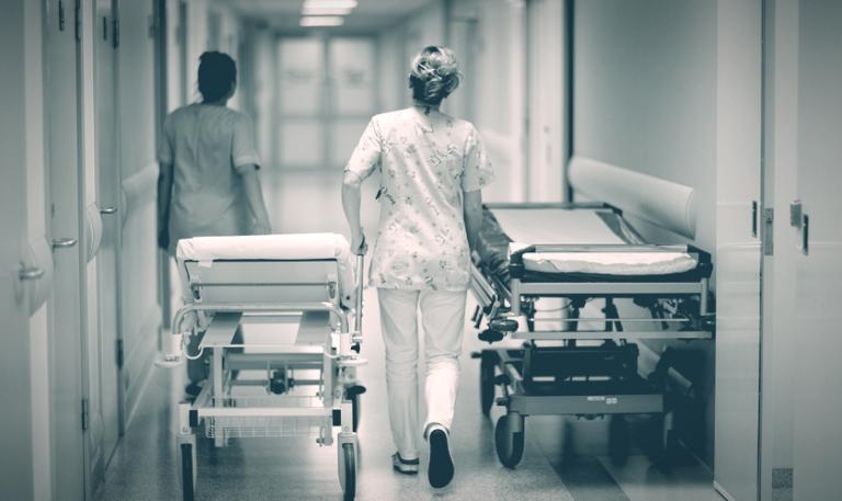 Two nurses wheeling a bed down a hospital corridor