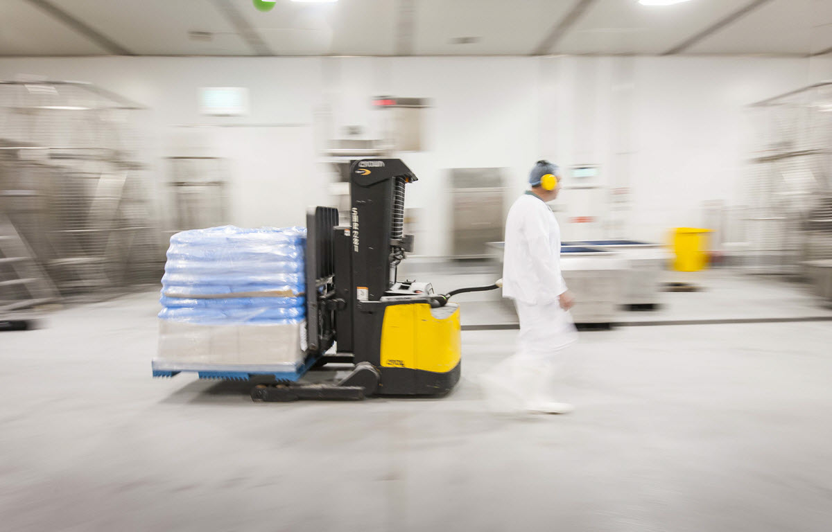 Worker operating an electric forklift in a warehouse