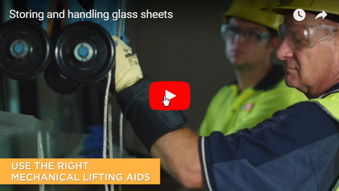 A man using mechanical aids to move glass sheets