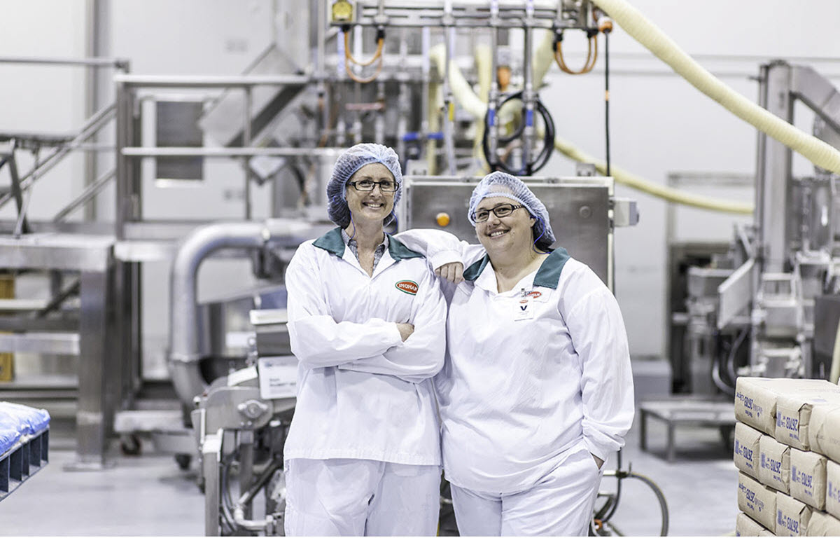 Two ladies standing together in a food factory