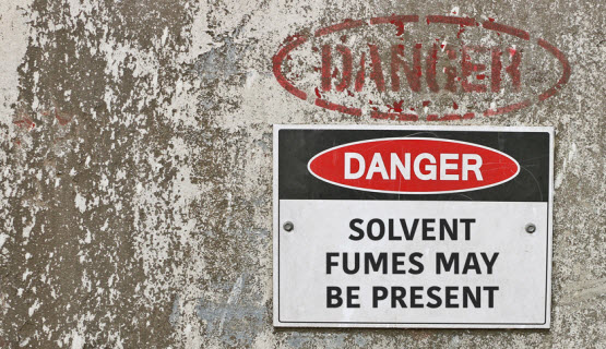 Sign on a concrete tank stating Danger: Solvent fumes may be present