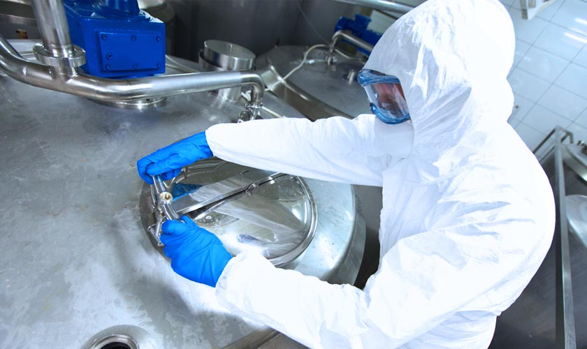 A person in a protective suit with goggles and gloves closing the lid on a large stainless steel vault