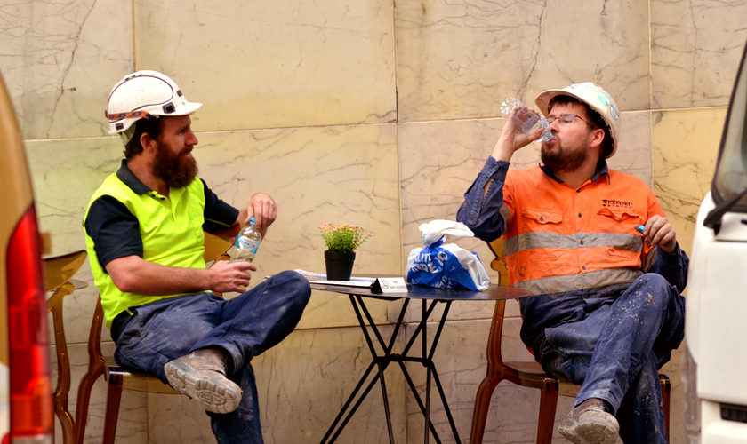 Two construction workers having a cool drink