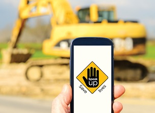 Image of a hand holding a mobile phone on a construction site