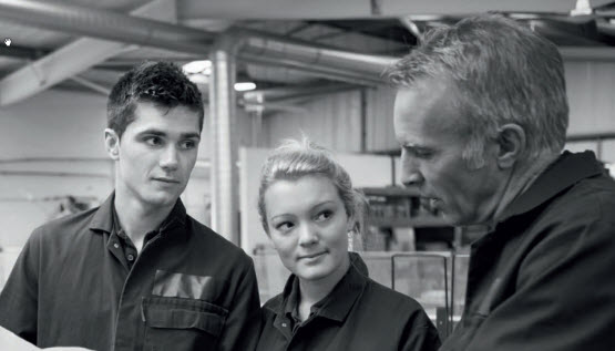 A supervisor talking with a young female and young male worker