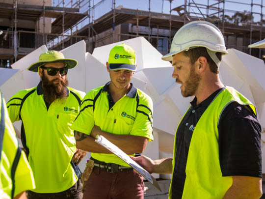 A group of tradesman on a construction site discussing safety