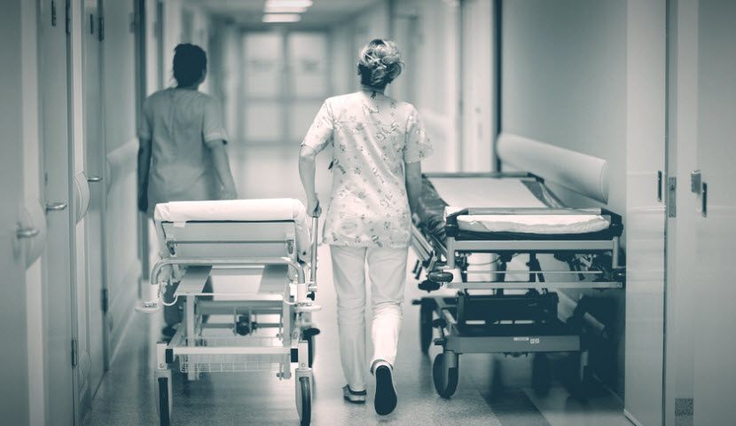 Two nurses wheeling hospital beds through a corridor