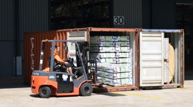 Image of driver unloading container with forklift - on even ground