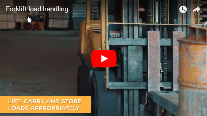 An orange forklift in a factory lifting a drum