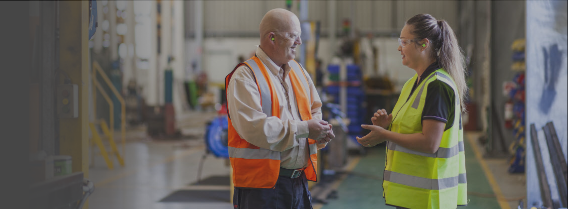 Two people talking in a warehouse